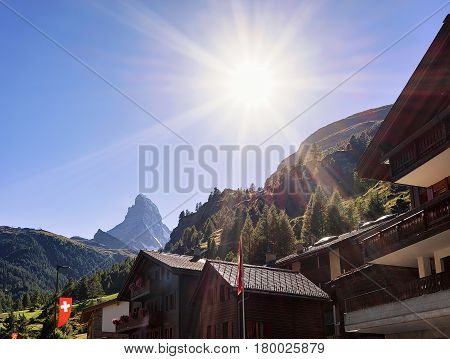 Traditional Swiss Chalets In Zermatt With Matterhorn Summit With Flags