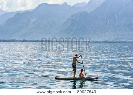 Montreux Switzerland - August 27 2016: Man and boy on Standup paddle surfing board on Geneva Lake in Montreux Vaud canton Switzerland
