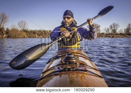 mature male paddler exercising with a wing carbon fiber paddle in a home built wooden sea kayak on lake, fall scenery  in Colorado, view from kayak bow