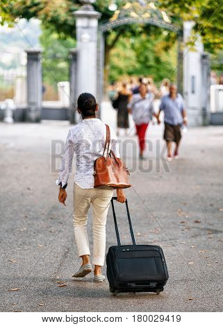 Woman with trolley luggage bag in Bern Switzerland