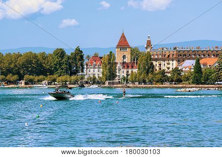 Lausanne Switzerland - August 26 2016: Motorboat and man wakeboarding at Lake Geneva embankment near Chateau Ouchy in Lausanne Switzerland.