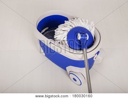 Mop And Blue Bucket For Cleaning Floor