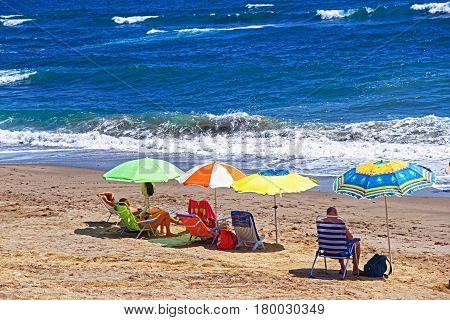 People sunbathing on the beach in the Mediterranean Sea in Marbella Andalusia Spain