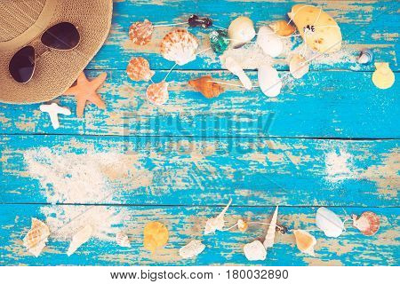 Summer background - The concept of leisure travel in the summer on a tropical beach seaside. sunglasses with starfish shells coral on wood table background. vintage color tone styles.