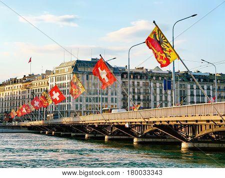 Geneva Lake and Mont-Blanc bridge with flags Geneva city center of Switzerland. People on the background