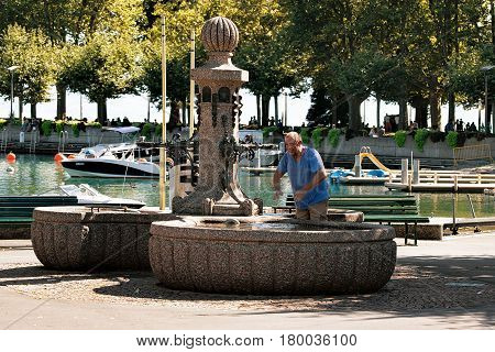 Senior Person Washing Hands In Fountain In Lake Geneva