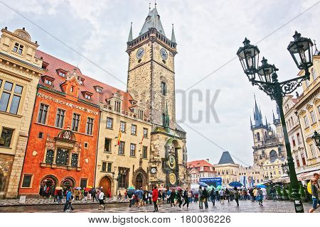 Tourists With Umbrellas At Old Town Hall In Rainy Prague