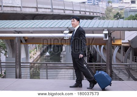 Asian Businessman Smiling And Happy, Wearing Suit With Luggage, Walking On Business Street For Trave