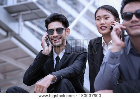 business man and woman happy sitting and using a cell phone and looking away business concept technology background