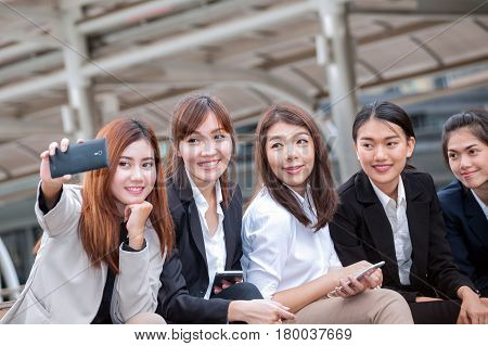 businesswoman sitting and using phone to take photo as selfie with colleague together and modern office building background