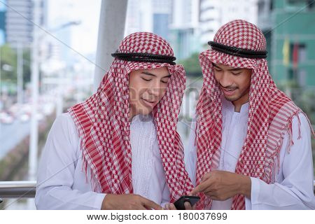 Arabian businessman using cell phone with colleauge for presenting business concept background