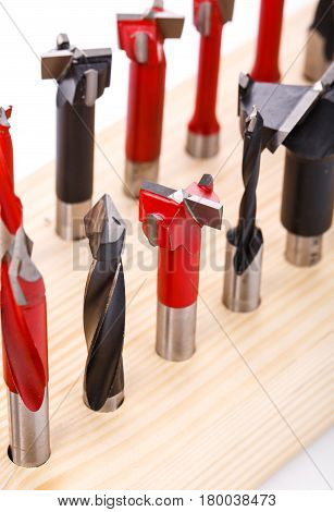 various shapes drill bits for wood on wooden stand. close-up macro photo