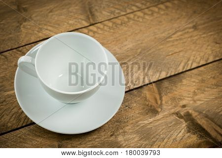 High angle view of an empty coffee cup on a wooden background. Text area for your message is available on the side.