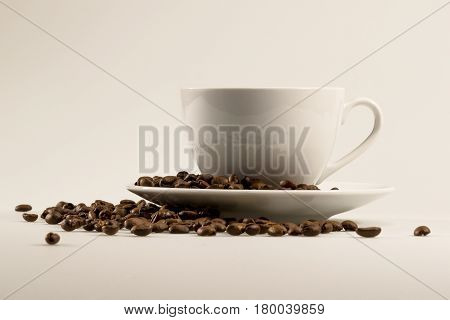 Side view of a coffee cup and beans on a white and gray background. Text area for your message is available on the side.