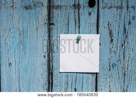 small blank white piece of paper hanging on wooden blue wall