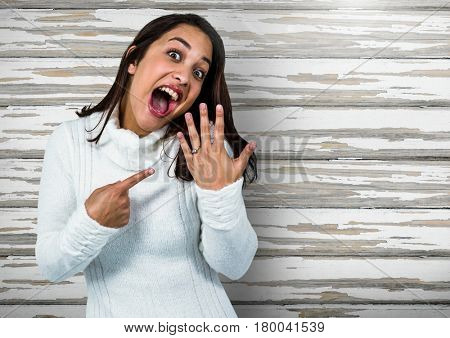 Digital composite of Engaged Woman with ring excited against wood