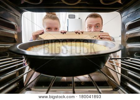 Young woman and young man staring at cheesecake into oven in kitchen. View from inside of the oven. Housewife and her husband holding the oven door.