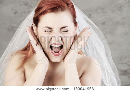 Funny red haired bride is screaming with hands up. Isolated on grey background.