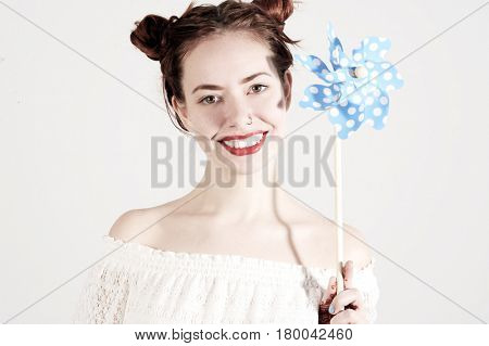 Lovely young girl is holding a windmill with innocent smile on her face. Studio shot on isolated white background.