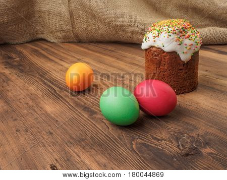 Easter bread. Easter cake and easter colored egg. Russian and Ukrainian, orthodox, slavic traditional Easter kulich on rural background from old wood and burlap. Selective focus.
