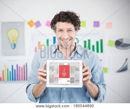 Businessman showing digital tablet with blank screen in creative office against composite image of rocket image on website
