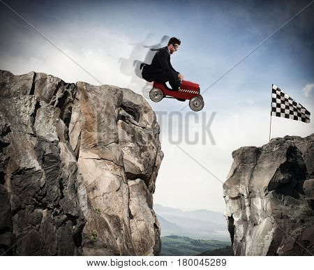 Businessman jumps between two mountains with a small car to get to the flag. Achievement business goal and Difficult career concept