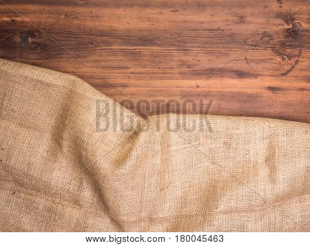 Old rural wooden table boards and burlap vintage background, photo top view. Hessian, sacking texture on wooden background for your design. Copy space for your message.