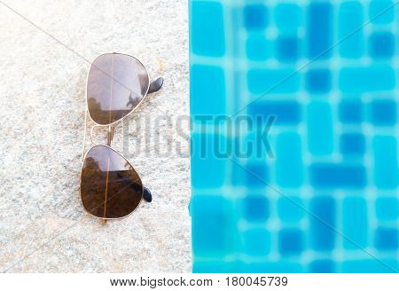 Sunglasses with natural light on poolside .