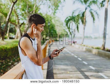 Attractive young sportsman listening to music from smartphone at public park.