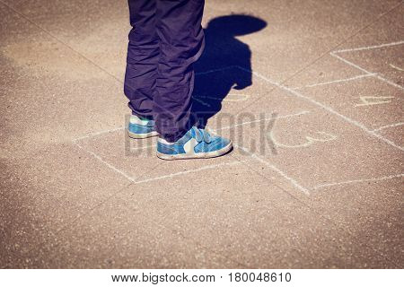 little boy playing hopscotch on playground, kids playtime