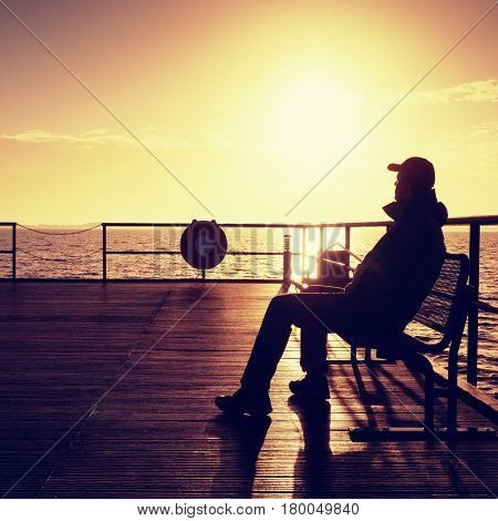 Man In Warm Jacket And Baseball Cap Sit On Pier And Enjoy Quiet Morning Sea. Tourist Relax.