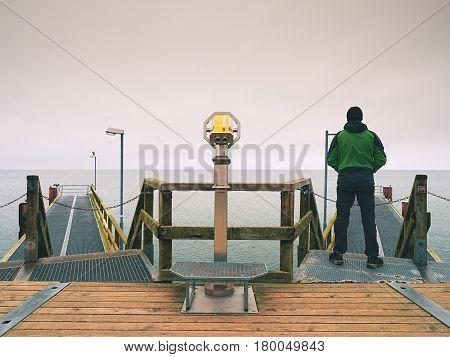 Man On Wooden Mole In Harbor Within Autumn Misty Day. Tourist At Handrail.