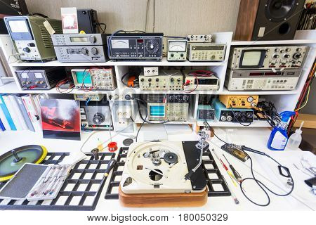 The full workbench of a hifi repairer with a disassembled turntable