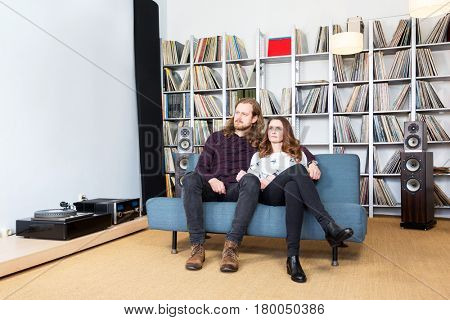a couple relaxing on the sofa listening to music