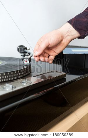 Carefully putting the needle on a vinyl lp record