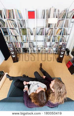 top view shot of a couple listening to music on the sofa