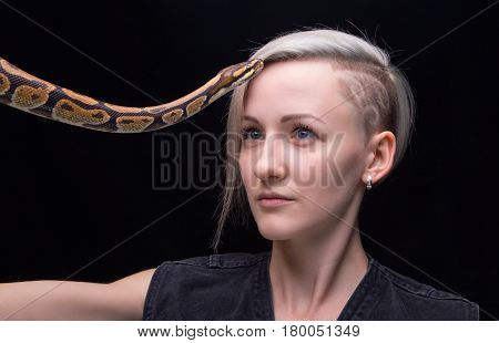 Portrait of blond woman with python on black background