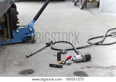 A lift jack under a car and work tools spread out on the floor outdoor cropped shot