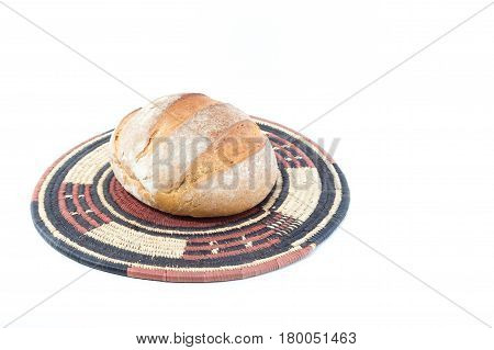 Crusty Loaf Of Bread On A Bamboo Straw Rustic Placemat Isolated On White Background