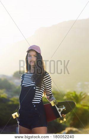 Sunlit skater girl in shorts with board portrait