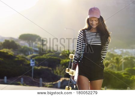Coolest girl in shorts holding skateboard smiling