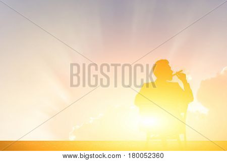silhouette of businessman hold cigar on sunset