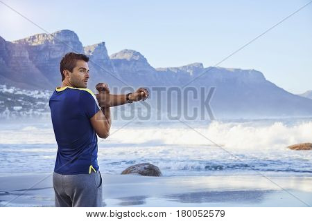 Handsome Athlete stretching at beach South Africa