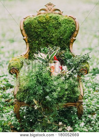 The green composition. The chair is overgrown with the moss and the huge bouquet is lying on it in the green grass