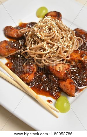 Soba noodles with chicken breast decorated with sesame seeds and grapes