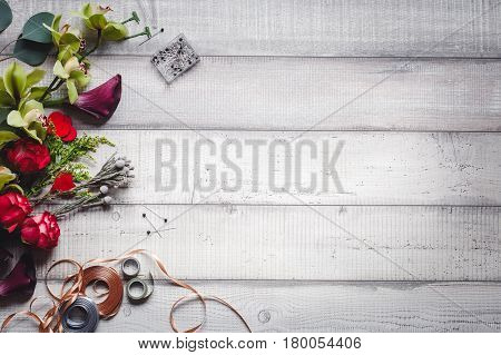 flowers, callas, carnations and ribbons on the side on white wooden table, space for text