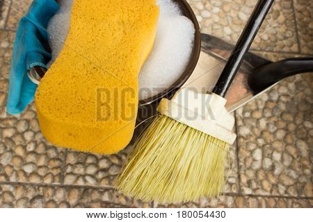 Bucket with water and soap. Sponge is in foreground and rights is broom and dustpan. Left on the bucket is hung rag.