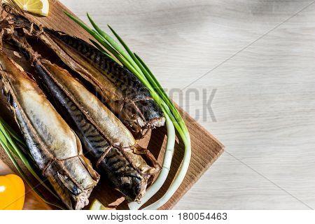Smoked fish mackerel on wooden hardboard on wooden table