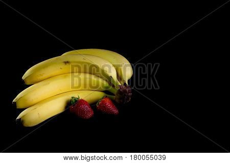 Four Fresh Golden Bananas With Two Strawberries Isolated In Dark Background