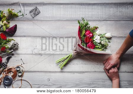 Bouquet of red roses, holding hands, love, callas, carnations and ribbons on the wooden table